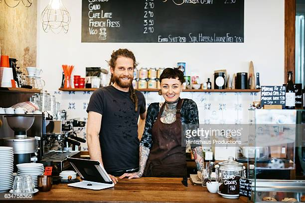 Two young people behind the counter of their café