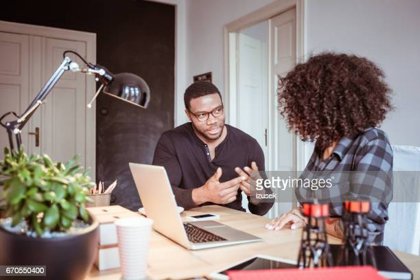 two young people brainstorming new business ideas - izusek stock pictures, royalty-free photos & images