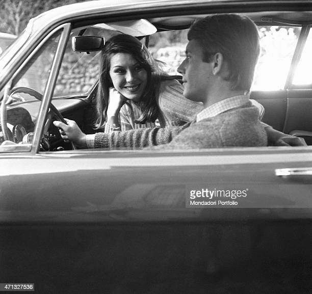 Two young people chatting seated into a car during one of their first dates. Know each other is a beautiful thing but it's hard to change even when...