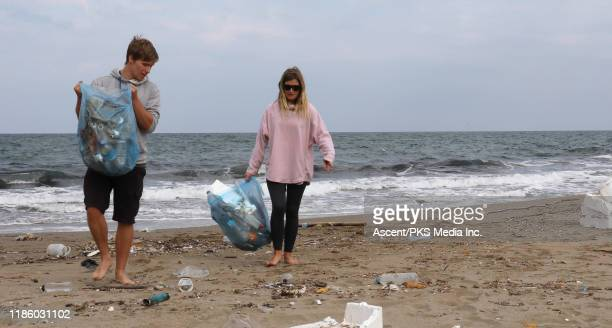two young people clean garbage off of beach - environmental issues imagens e fotografias de stock
