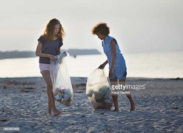 two young people collecting trash on beach - levantando - fotografias e filmes do acervo