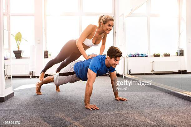Two young people doing balance exercises on Pilates class.