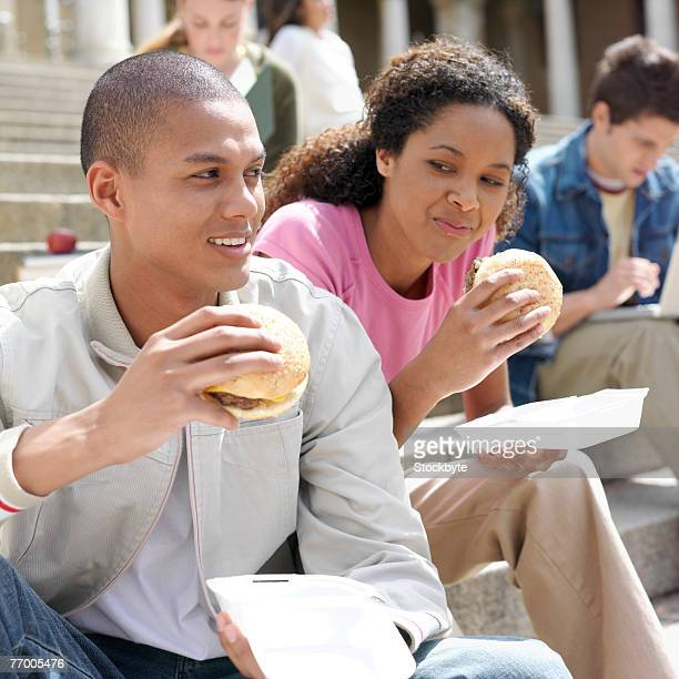 Two young people eating hamburgers, sitting on steps