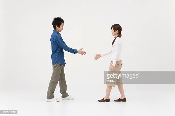Two young people extending handshake