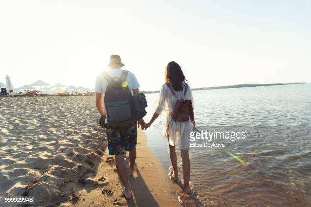 Two young people holding hands and walking on beach
