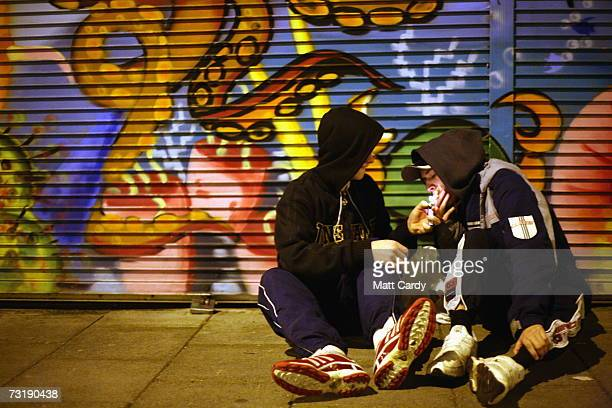 Two young people in hooded tops share a cigarette outside a shop on the Southmead housing estate February 1 Bristol England Bristol City Council is...