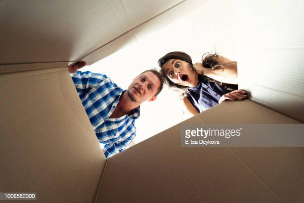 two young people looking surprised into a carton box - women wearing see through clothing stock pictures, royalty-free photos & images