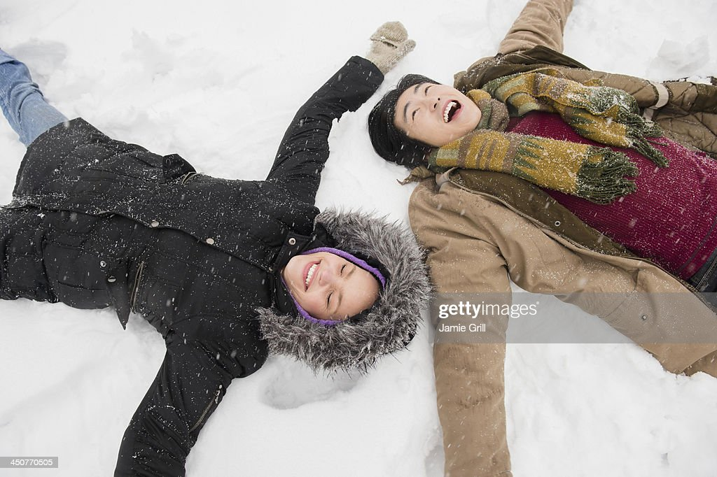 Two young people making snow angels : Stock Photo