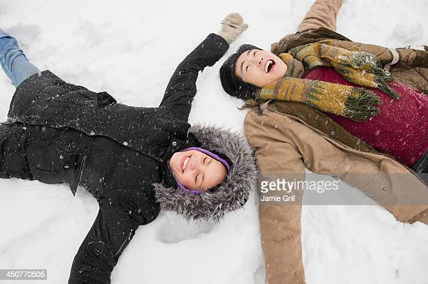 two young people making snow angels - snow angel stock photos and pictures