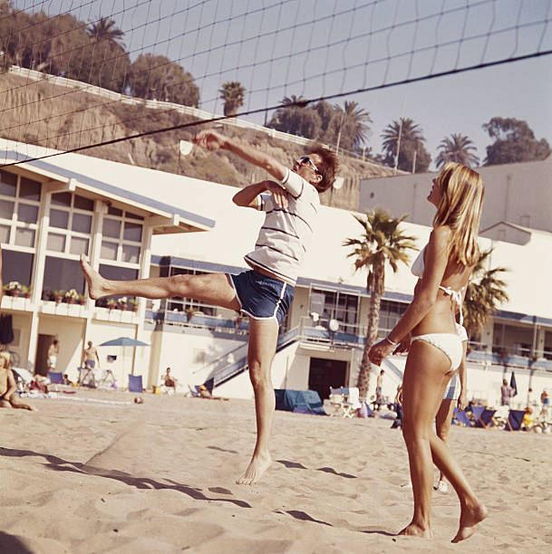 Two young people playing volleyball on beach