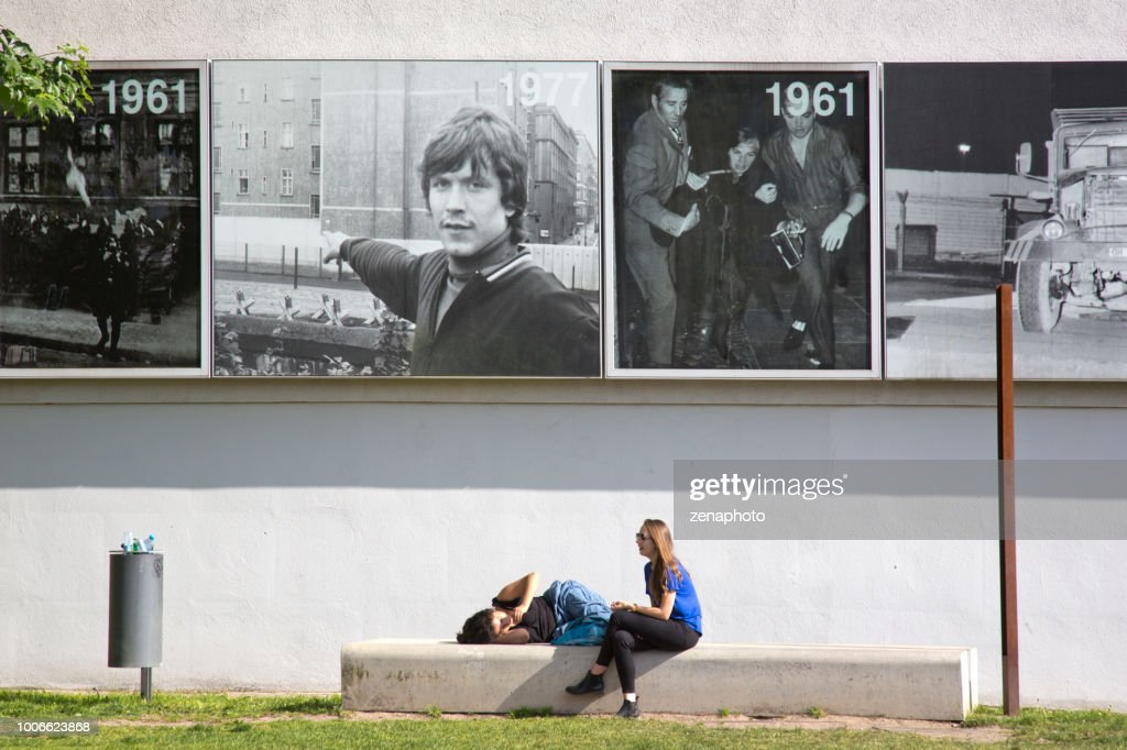 Two young people resting at the Bernauer Strasse memorial : Stock Photo