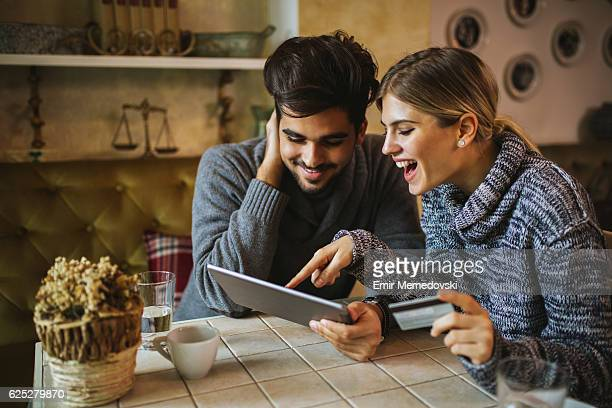 Two young people shopping online using digital tablet