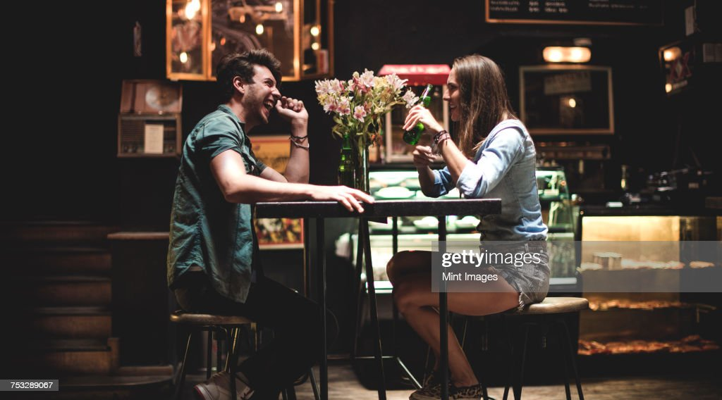 Two young people sitting at a table in a bar. : Stock-Foto