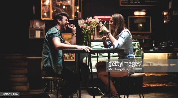 Two young people sitting at a table in a bar.