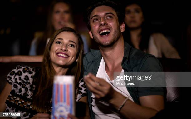 Two young people sitting in a cinema watching a film and eating popcorn.