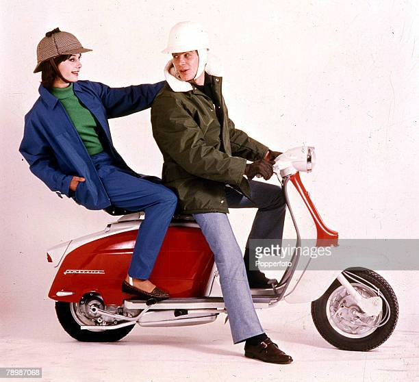 1963 Two young people sitting on a Lambretta scooter wearing suitable fashionable clothing and stylish helmets the man is looking back at the woman...