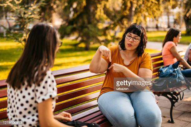 two young people speak in sign language - signing stock pictures, royalty-free photos & images
