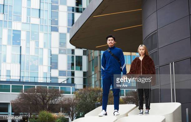 two young people standing on concrete structure holding hands. - hands in her pants fotografías e imágenes de stock