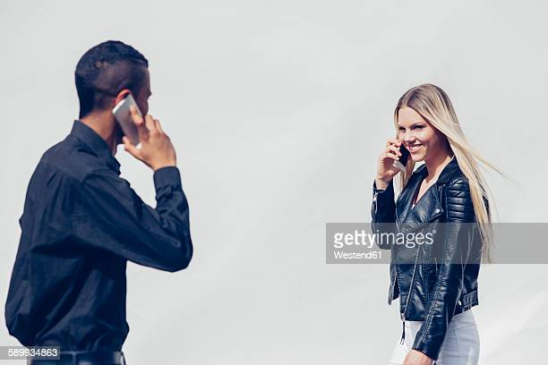 Two young people telephoning with smartphones watching each other