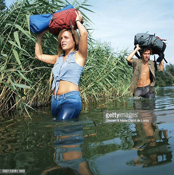 two young people wading through river, bags resting on heads - open blouse - fotografias e filmes do acervo
