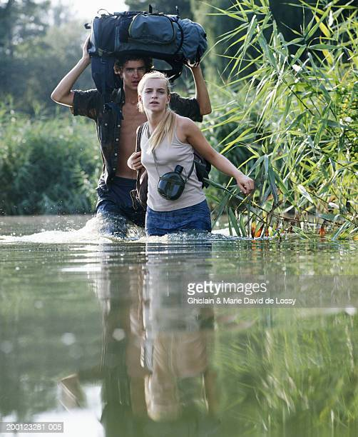 two young people wading through river, man carrying bag over head - waist deep in water stock pictures, royalty-free photos & images