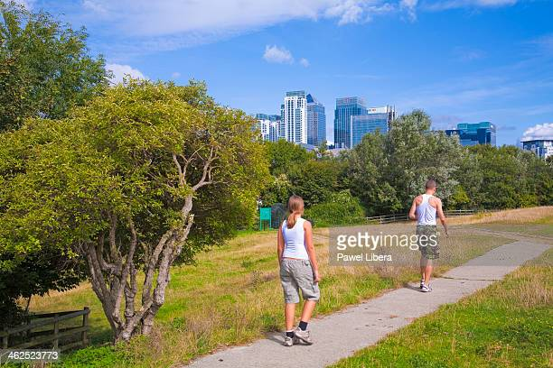 Two young people walking through city farm in London Docklands with Canary Wharf Financial Centre in the background