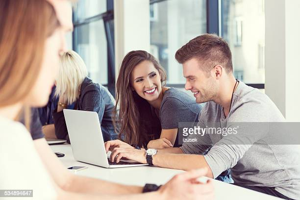 two young people working on laptop together - izusek stock pictures, royalty-free photos & images