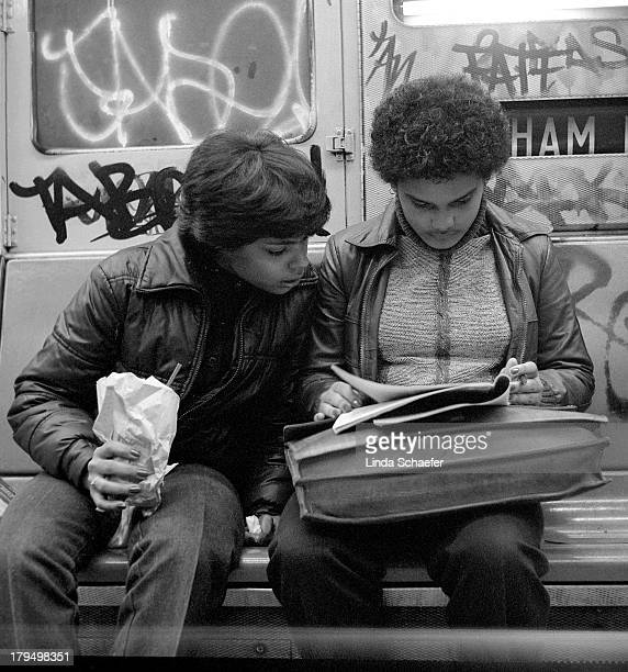 Two young people working on school work inside a New York City subway train in 1982. The train is covered with graffiti as was typical at that time....