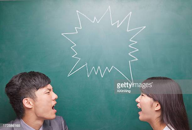 Two young people yelling at each other in front of blackboard