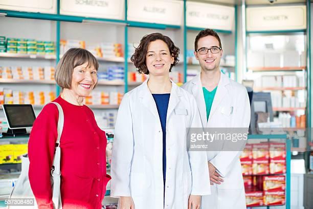 Dois jovens farmacêuticos com senior cliente