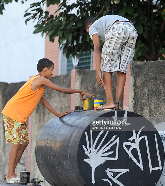 Two young photography students use their pin hole cameras during a street class at the favela da Mare shantytown in Rio de Janeiro Brazil on August...