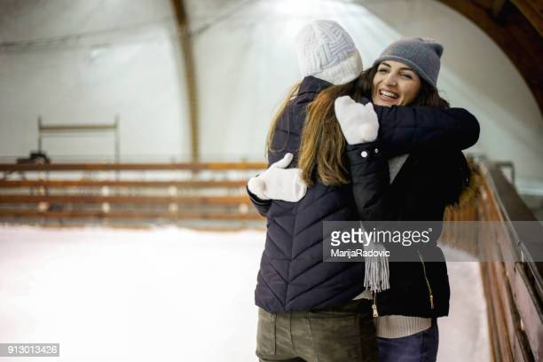 Two young positive women on ice rink holding hands to support each other