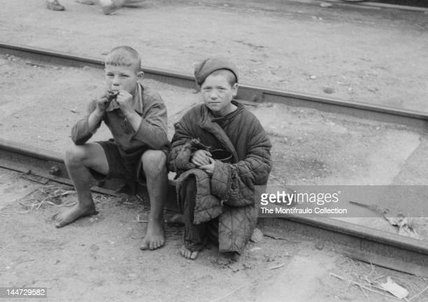 Two young raggedy dressed and barefooted Russian boys sitting on a railway track during World War II Eastern Front Russia 1941