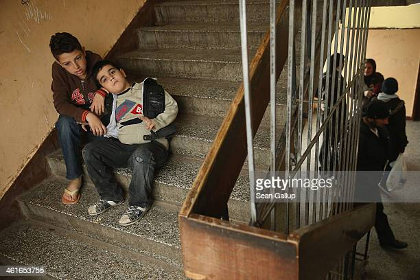 Two young refugee boys from Syria sit on a staircase at the main refugee center on January 9, 2014 in Sofia, Bulgaria. Approximately 850 refugees,...