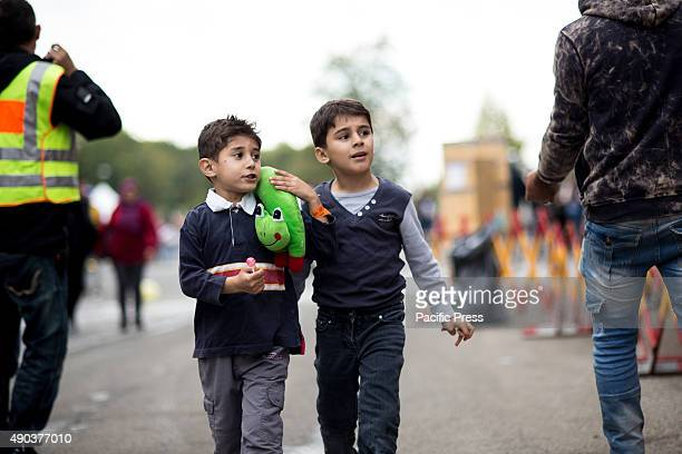 FREILASSING BAVARIA GERMANY Two young refugees play around with volunteers police and press Thousands of migrants escape from their countries due to...