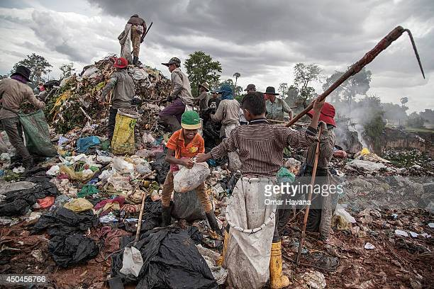 Two young scavengers fight for a piece of plastic that they found while working between tons of trash in the Anlong Pi landfill on June 11 2014 in...
