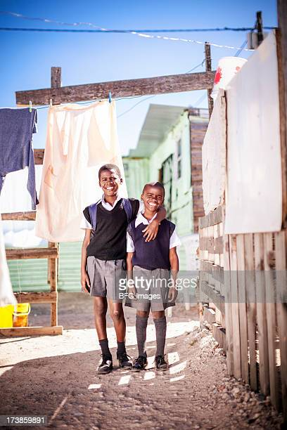 Two Young school boys standing outside township shack