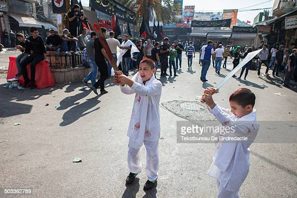 Two young shiite muslim boys, taking part in the ritual of self-flagellation and injuring themselves by cutting their foreheads with traditional...
