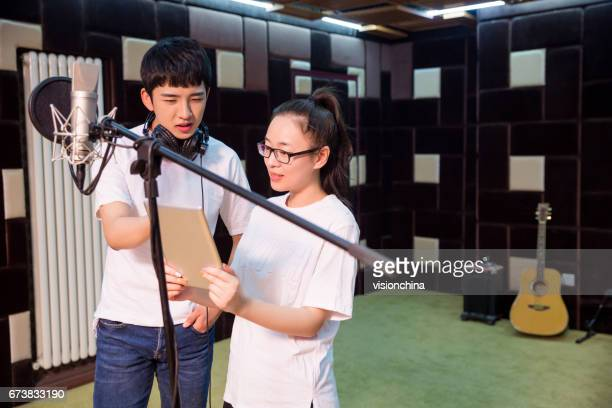 two young singers recording vocals in studio
