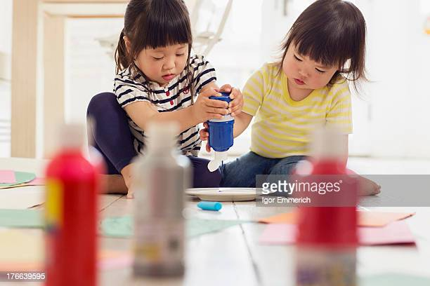 Two young sister squeezing paint from bottles