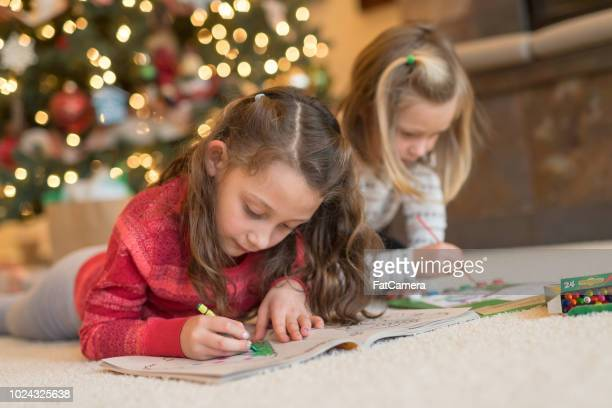 Two young sisters draw in their coloring books in front of the Christmas tree