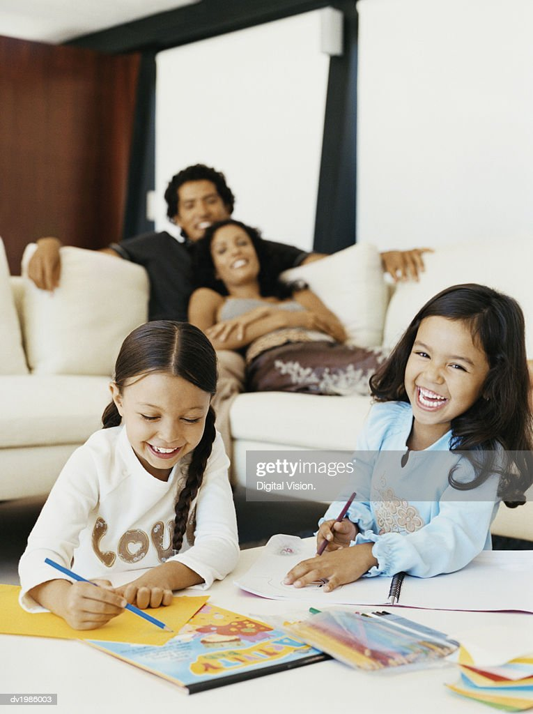 Two Young Sisters Drawing in a Living Room with Their Parents Sitting on a Sofa in the Background : Stock Photo