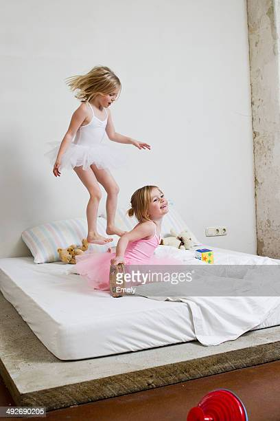 Two young sisters dressed as ballet dancers playing on bed