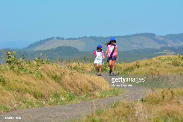 Two young sisters holding hands hiking