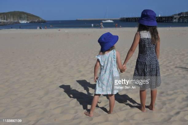 two young sisters holding hands walking to the beach - rafael ben ari stock-fotos und bilder