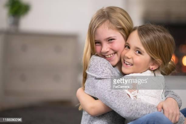 zwei junge schwestern hugging - schwester stock-fotos und bilder