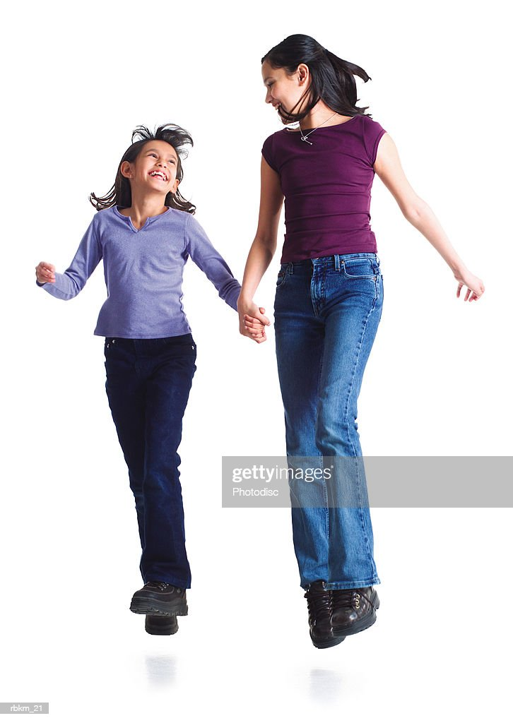 two young sisters jump into the air laughing while holding hands : Stockfoto