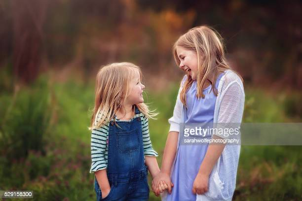 two young sisters laughing with each other