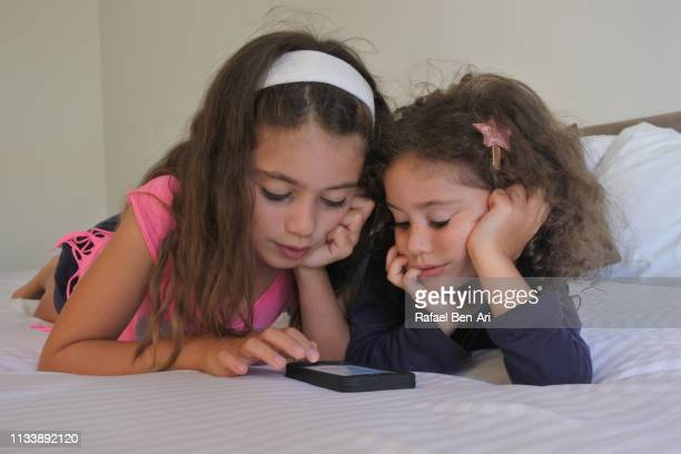 two young sisters laying on bed playing on mobile phone - rafael ben ari 個照片及圖片檔