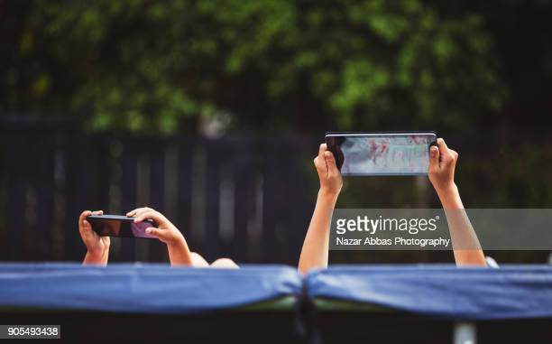 Two young sisters on trampoline playing on tablets.
